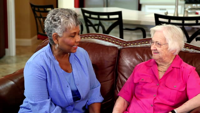 Two senior adult women friends visiting at home. video