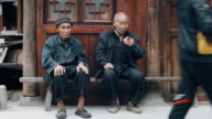 Two senior Chinese adults sitting on a bench video