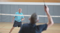 Two senior male friends playing indoor badminton video