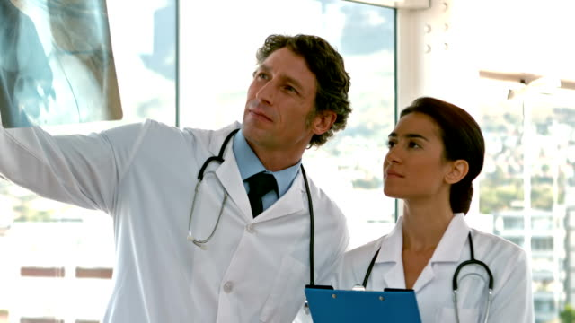 Two serious doctors looking at Xray video