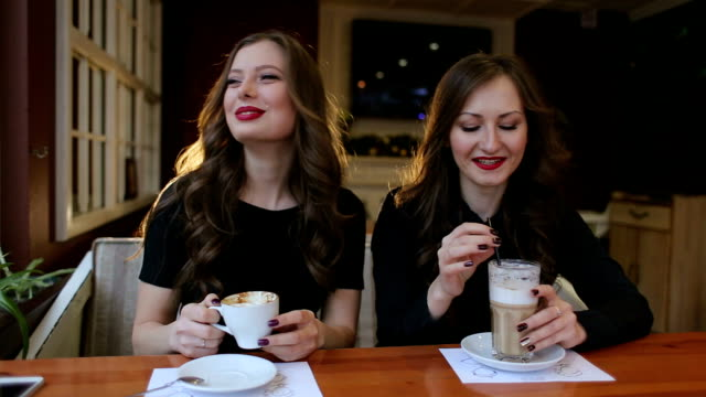 Two sexy girls drinking coffee in cafe, close-up. video