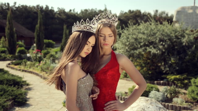 Two sexy young women posing in evening gowns and crowns in a beautiful garden video
