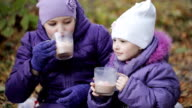 two sisters drink cocoa with marshmallows in the autumn park video