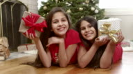 Two sisters lay on the floor in front of the christmas tree and hold up their presents. Portrait video