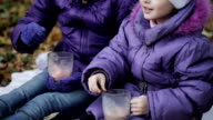 two sisters mix cocoa with marshmallows cups. Girls laugh video