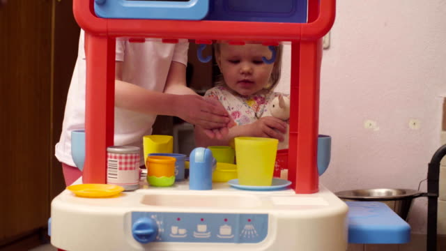 Two sisters playing in toy kitchen video