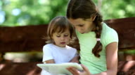 Two sisters with white tablet PC sits on the swing bench in garden video