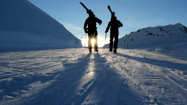 Two skiers walking towards the falling sun video