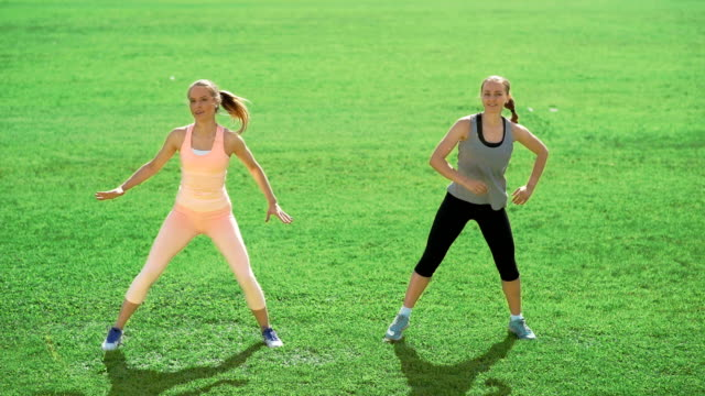 Two slim athletic women doing exercises on green grass video