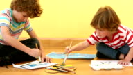 Two small boys painting pictures video
