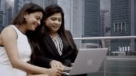 Two Smiling Businesswomen Using Laptop Outdoors video
