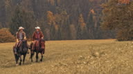 SLO MO Two smiling ranchers riding horses in mountain meadow video