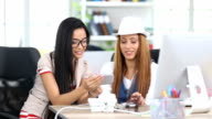 Two smiling women talking and using smart phone in workplace video