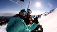 Two snowboarders riding up ski lift video