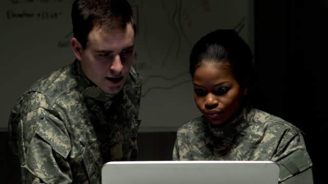 Two soldiers looking at a laptop and discussing. video