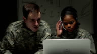 Two soldiers looking at a laptop communicating through headset. video