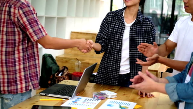 Two start up young people shaking hands after successful meeting while their colleagues applauding - teamwork business applause concept double exposure with chess video