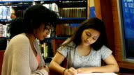 Two STEM female high school students work on assignment together in library video