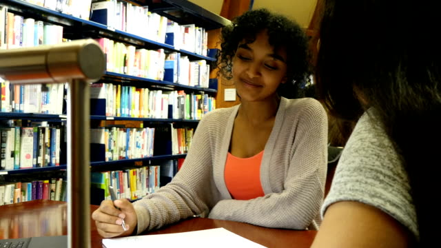 Two STEM high school female students work on assignment together video