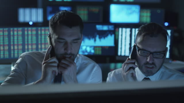 Two stockbrokers are actively talking on phones while working on computers in a dark office filled with display screens. video