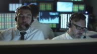Two stockbrokers are talking on a headset while working on a computer in a dark office filled with display screens. video
