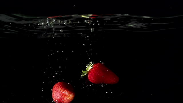 Two strawberryes  drop into water in slowmotion video