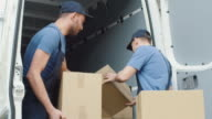 Two Strong Delivery Men Loading Commercial Vehicle Full of Cardboard Boxes in Slow Motion. video