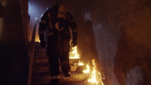 Two Strong Firefighters Going Up The Stairs in Burning Building. Stairs Burn With Open Flames. In Slow Motion. video
