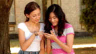 Two students discussing pictures in mobile phone video