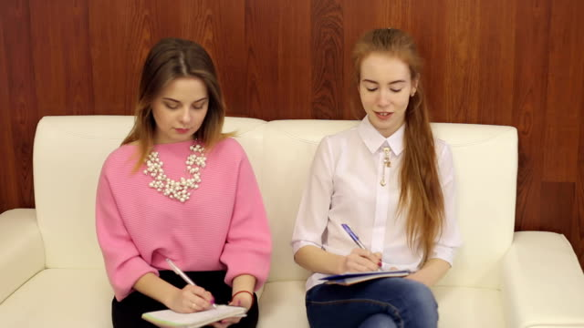 Two students writing in notebooks in master class. video