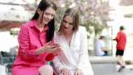 Two stylish women friends looking to smartphone in city video