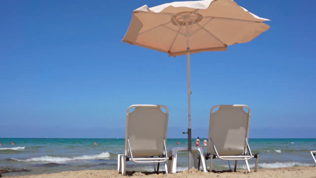 Two sunloungers standing on beach video
