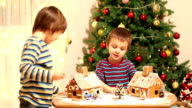 Two sweet boys, brothers, making gingerbread cookies house, decorating at home in front of the Christmas tree, child playing and enjoying, Christmas concept video