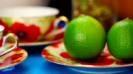 Two Tea cups with green lime near video