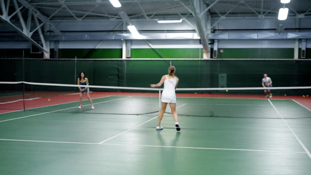 Two teams playing tennis in double game. Women and men players practicing video