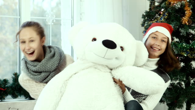 Two teen girl hiding behind the bear and smiling at the camera video
