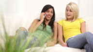 Two teen girls using cell phone together video
