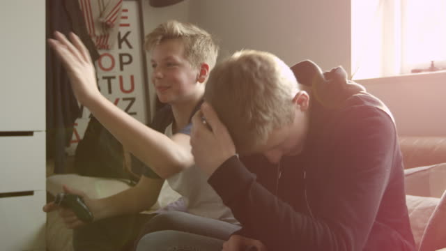 Two Teenage Boys Playing Video Game In Bedroom Shot On R3D video