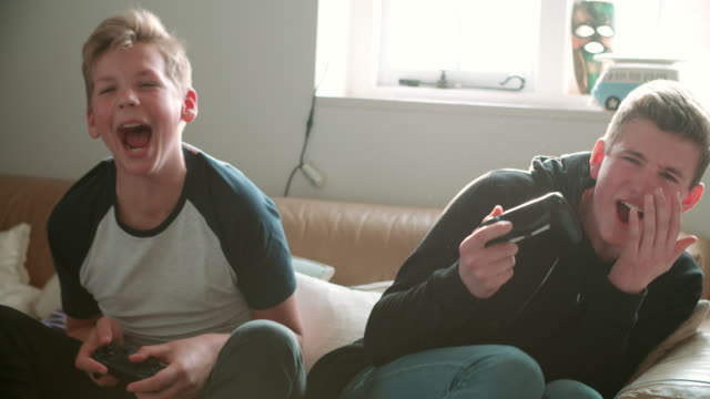 Two Teenage Boys Playing Video Game In Bedroom video