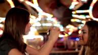 two teenage girlfriends having fun in amusement park video