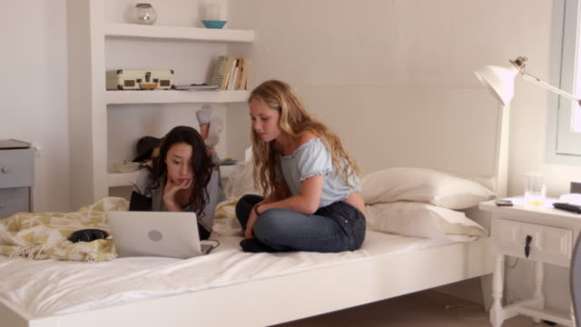 Two teenage girls sitting on bed using a laptop computer, shot on R3D video