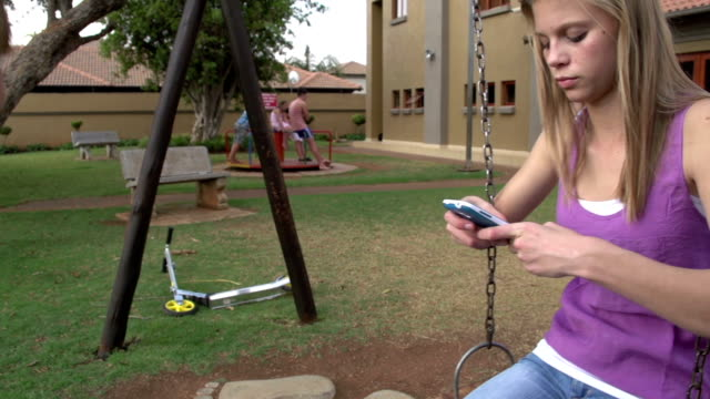 Two teenagers in park on swing,one texting on smartphone video