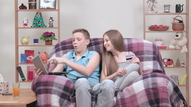 Two teenagers making online shopping in the internet indoors video