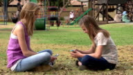 Two teenagers sitting in park texting on smartphones video