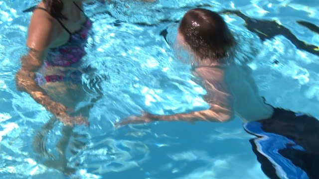 Two teens talk at outdoor pool video