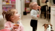 two toddler boy and girl watching TV and eating muffin video