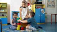 Two toddler children build tower of colorful plastic blocks video
