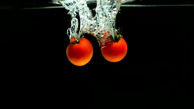 Two tomatoes falling in water video