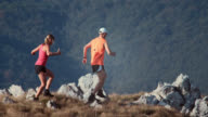 Two trail runners going down the grassy plateau video