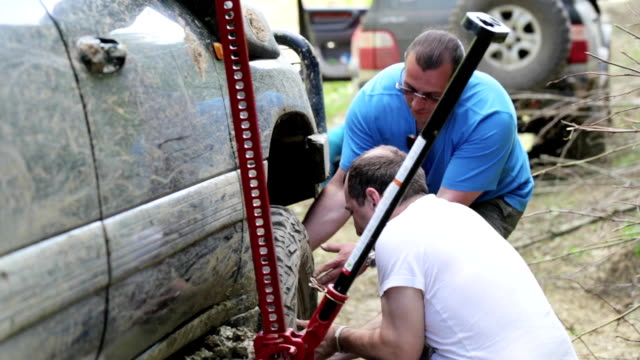 Two travelers replacing wheel of expeditionaty SUV at forest dirty road. video